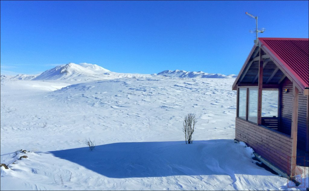 """This is the little cottage """"R50"""" that I rented. Cheaper than the car rental, and a great view of Hekla about 20 km away. It's super hard to gauge distance without trees as a reference. (Note the two trees attempting to grow in the from of the cottage.)"""