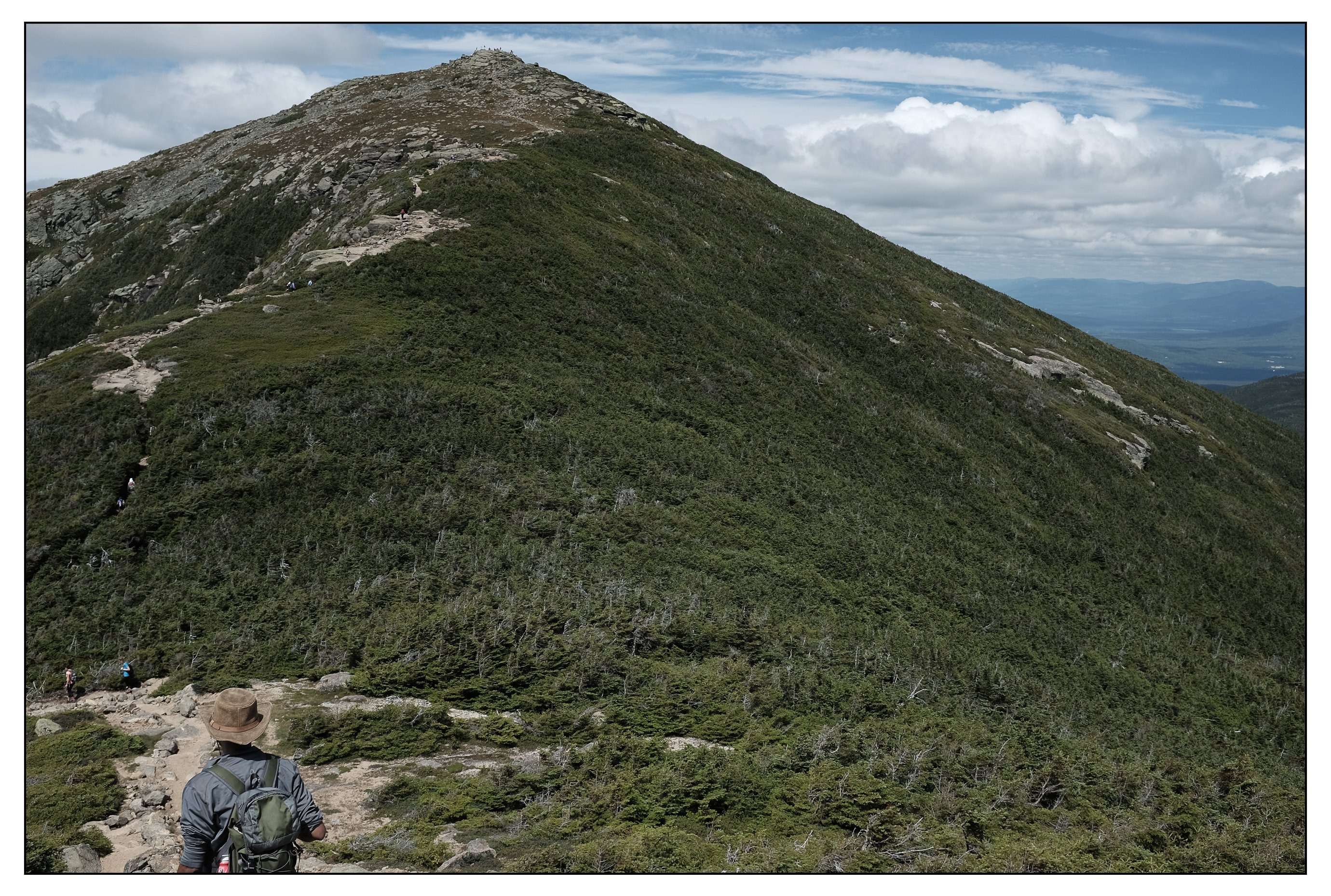 First clear view of the Mt. Lafayette summit after emerging from the forested ridge connecting Mt. Garfield and Mt. Lafayette. Note the inherent fashionability of this NH hiker on his way to the summit.